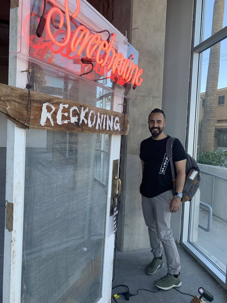 Ali Fathollahi stands next to his exhibit in the downtown area that will be available for viewi ...