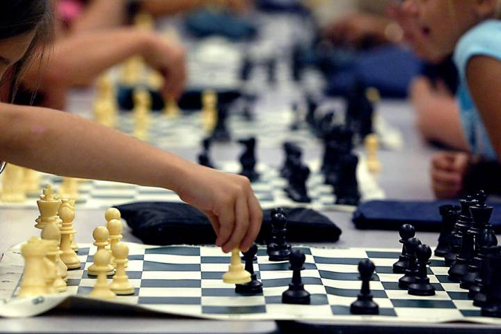 Groups of children play chess at the Wengert Elementary School during a Clark County Parks and ...