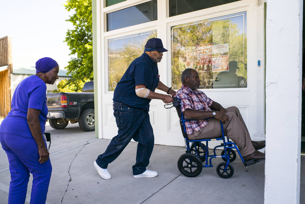 Paul Browning pushes the wheelchair of his brother, Tony, while his mother, Betty, looks on, as ...