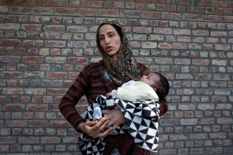Ulfat, a Kashmiri woman holds her forty days old daughter Tanzeela, as she waits outside a poli ...