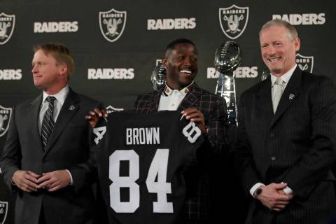 Oakland Raiders wide receiver Antonio Brown, center, holds his jersey beside coach Jon Gruden, ...