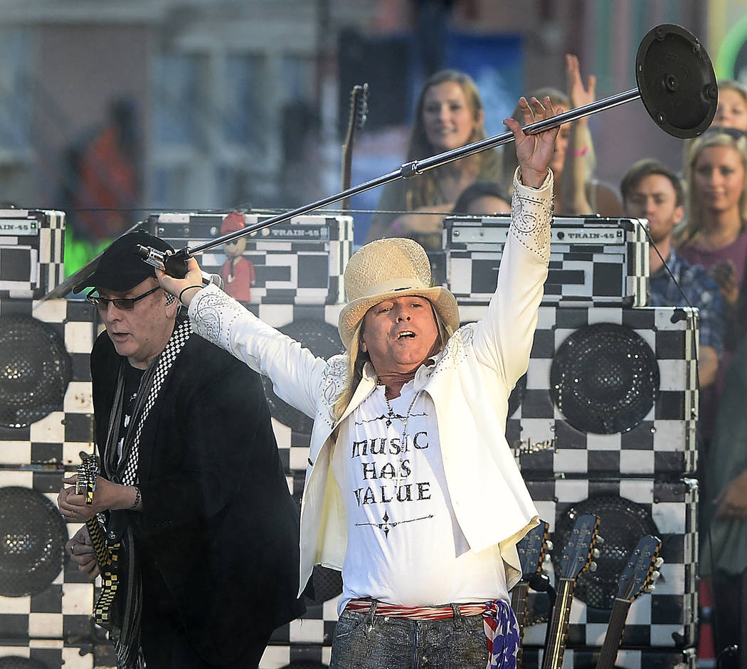 Rick Nielsen, left, and Robin Zander of Cheap Trick perform on an outdoor stage during the CMT ...