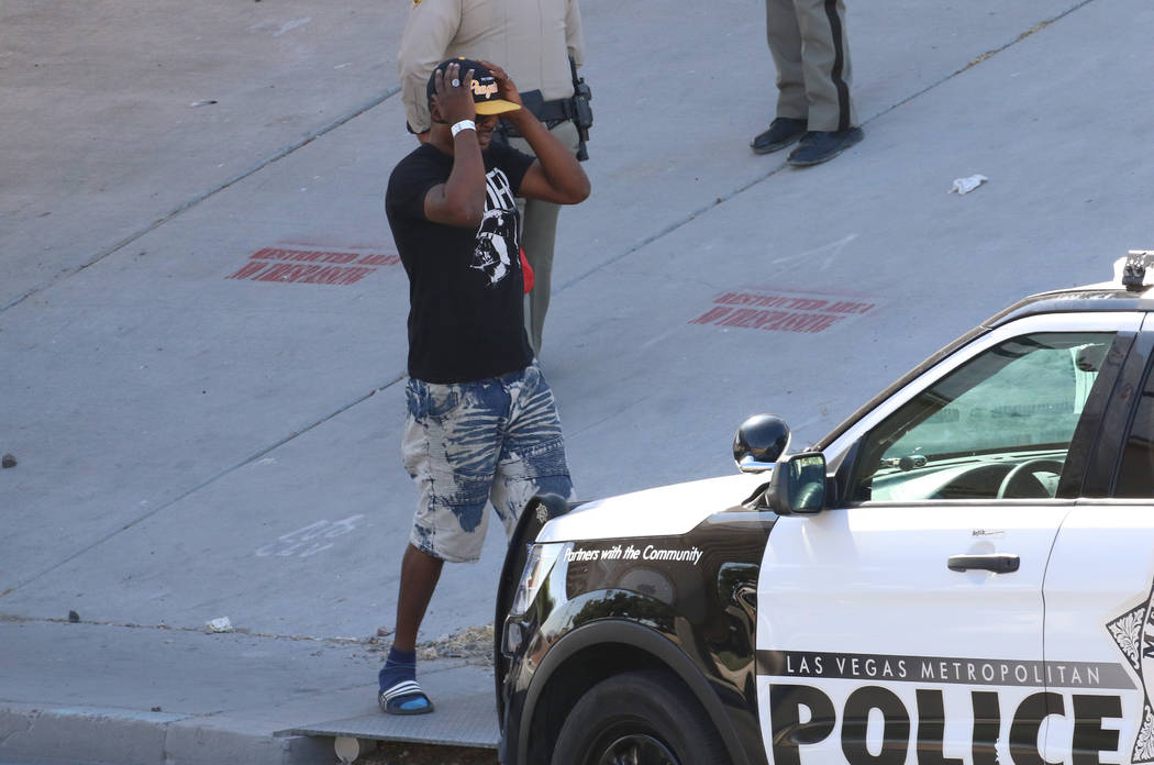 A man reacts at the scene where Las Vegas police are investigating after a person was struck an ...