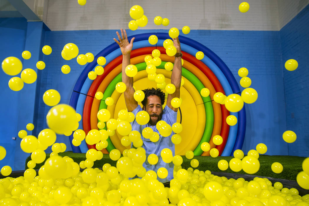 Bryce Hill pops up from the ball pit in the Pot of Happiness Room at the new Happy Place popup ...