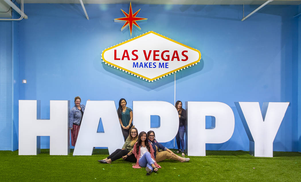 Friends strike poses about the signs in the Happy Room at the new Happy Place popup at Mandalay ...