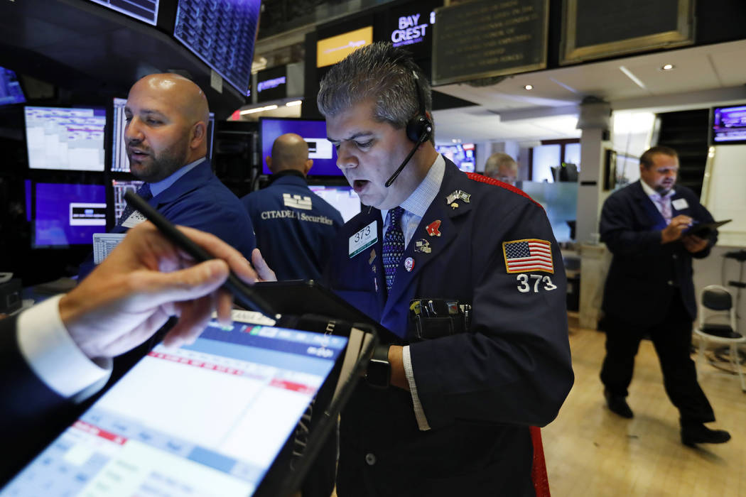 Trader John Panin, center, works on the floor of the New York Stock Exchange, Wednesday, Aug. 2 ...
