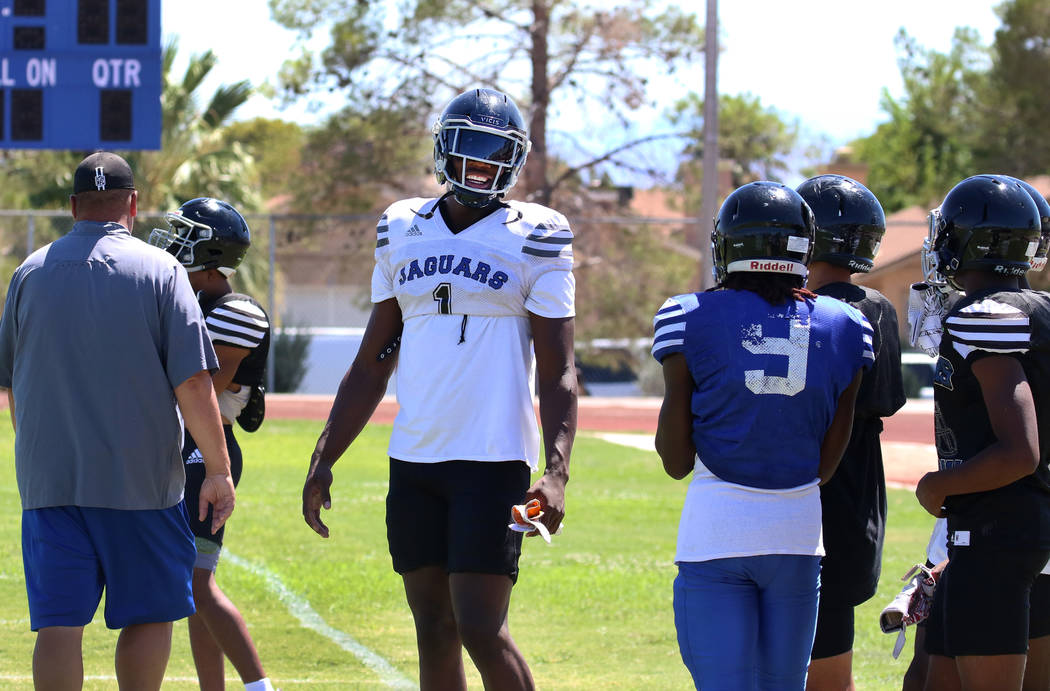 Desert Pines High School defensive lineman Darnell Washington (1) chats with his teammates befo ...