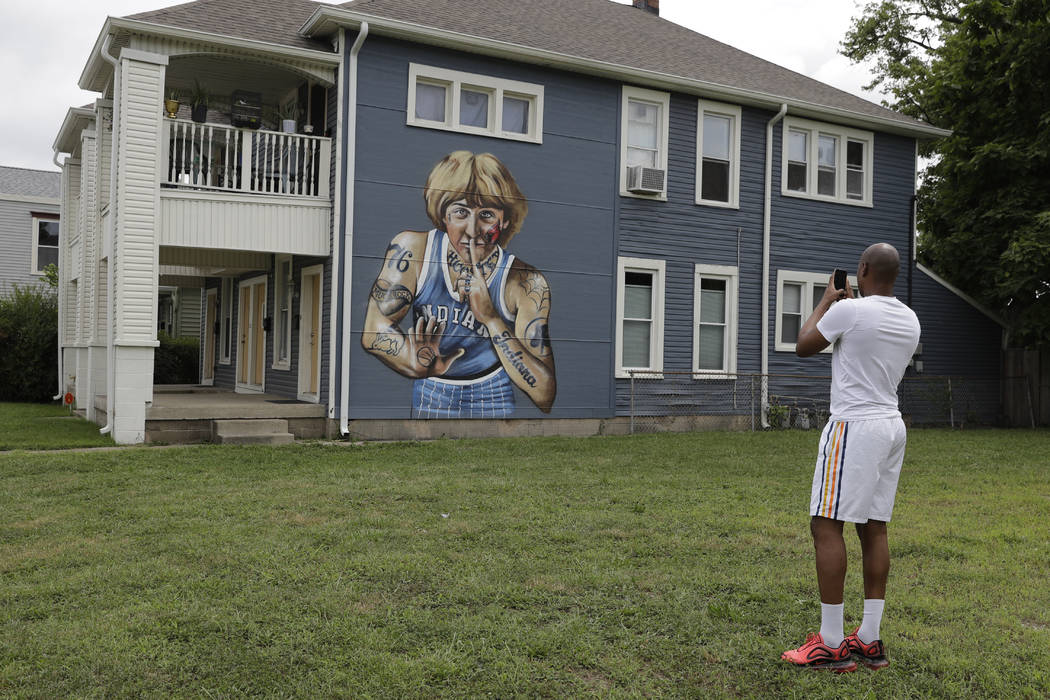 D'Andre Peyton takes a photo of a mural of former NBA star Larry Bird on the side of a multi-fa ...