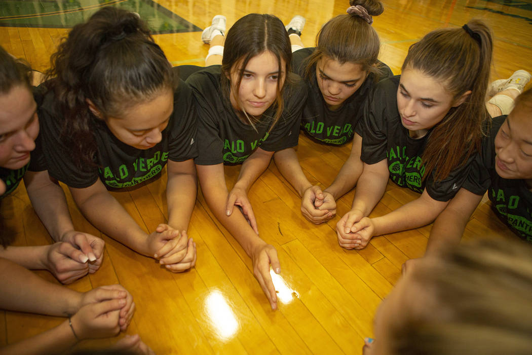 Team captain Carli Tanner, center, 17, senior, sticks her hand out for the rest of the volleyba ...