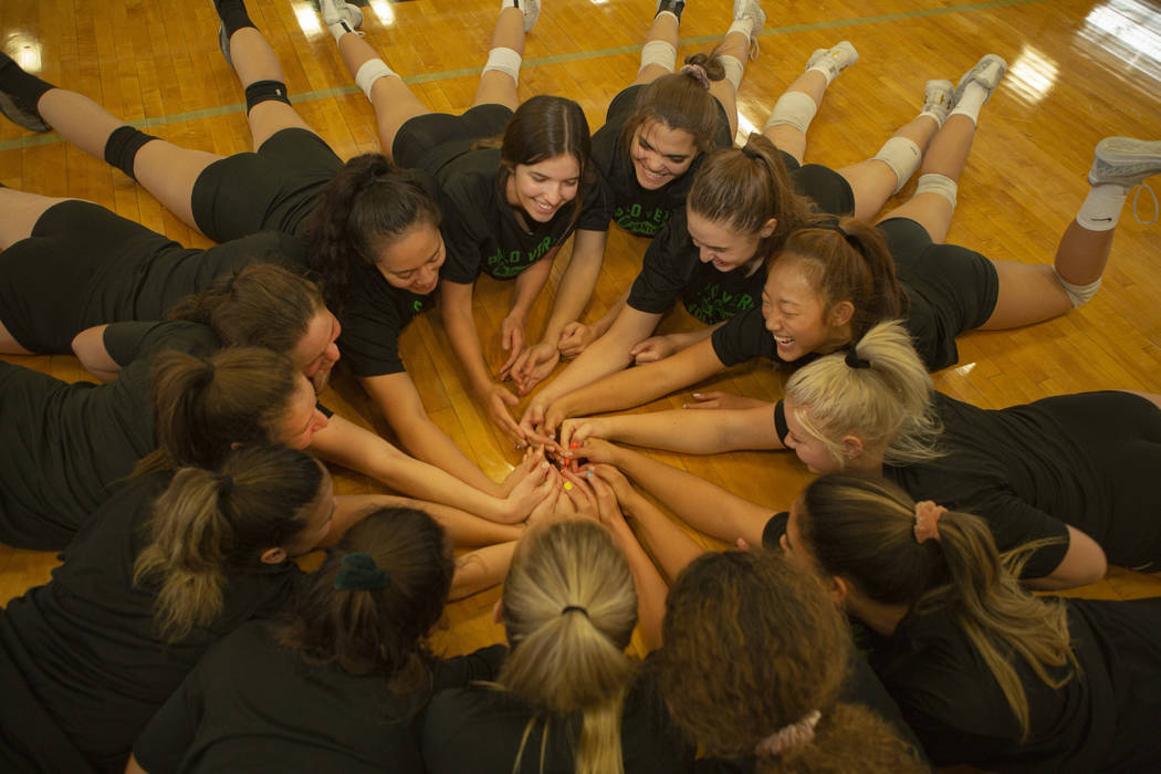 The varsity volleyball team all make a makeshift with their hands to symbolize what area of the ...