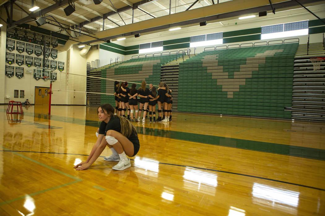 Team captains Carli Tanner, 17, senior, stretches while the junior varsity team, background, hu ...