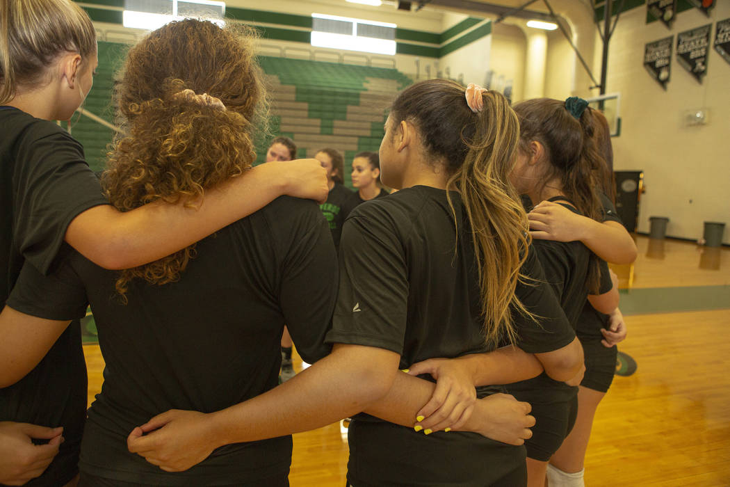 The varsity volleyball team embrace while listening to their coach during practice at Palo Verd ...
