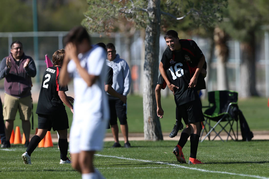 Las Vegas' Sergio Aguayo (18) is lifted up by Nathan Zamora (16) in celebration after his goal ...