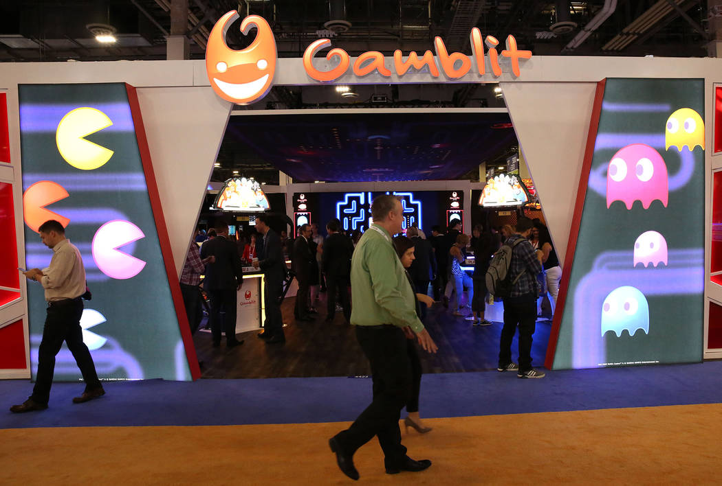 Expo goers walk past the Gamblit Gaming booth during Global Gaming Expo at the Sands Expo and C ...