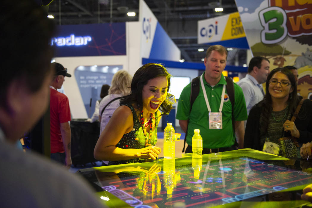 Nikki Tuazon shows attendees how to play the new Gamblit Pac-Man game at the 18th annual Global ...