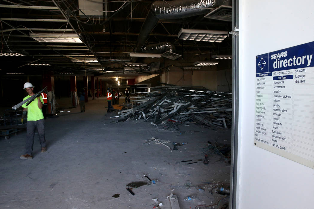 Workers, including John Duncombe, recycle building material inside the former Sears store is sh ...