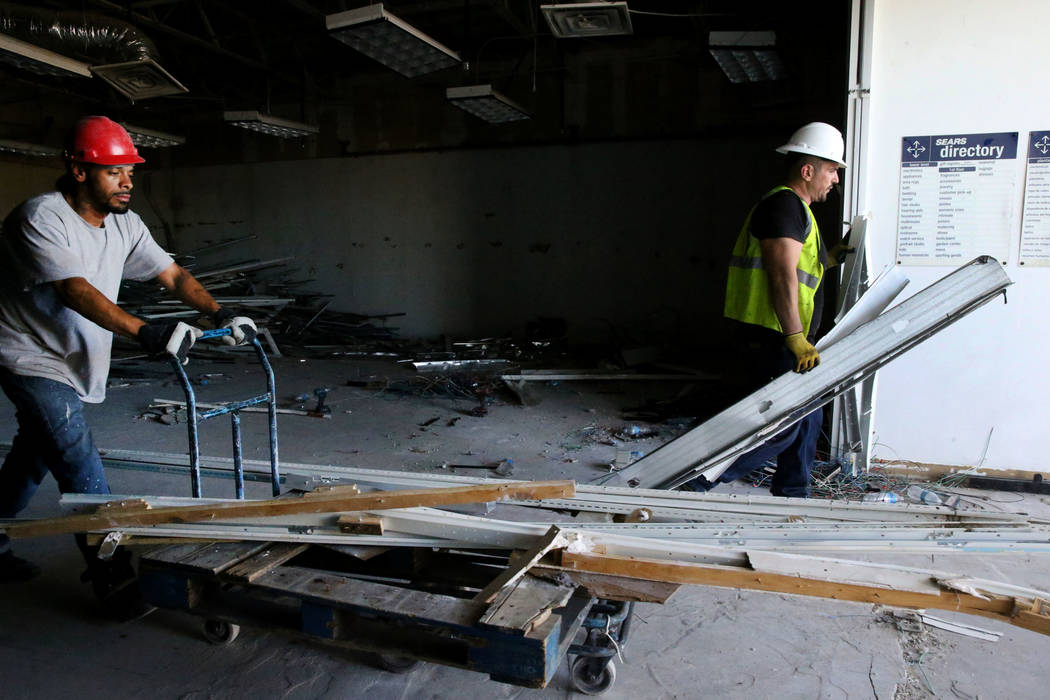Workers Ivan Cruz, left, and Mike Istrate recycle building material inside the former Sears sto ...