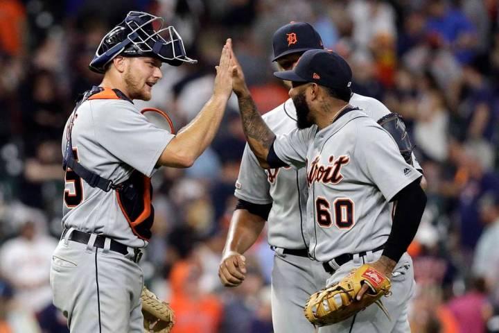 Detroit Tigers' John Hicks, left, celebrates with Ronny Rodriguez (60) and Joe Jimenez after a ...