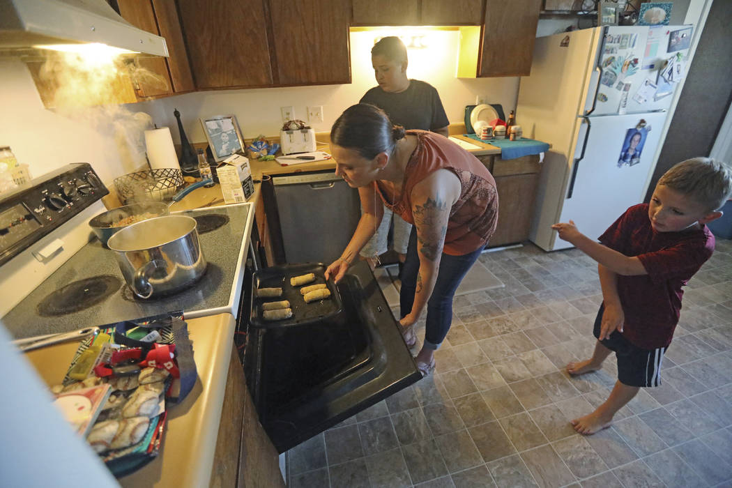 Misty Dotson prepares dinner for her son's at their home Tuesday, Aug. 20, 2019, in Murray, Uta ...