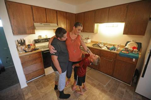 Misty Dotson hugs her son's at their home Tuesday, Aug. 20, 2019, in Murray, Utah. Dotson is a ...
