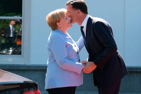 Dutch Prime Minister Mark Rutte, right, greets German Chancellor Angela Merkel in The Hague, Ne ...