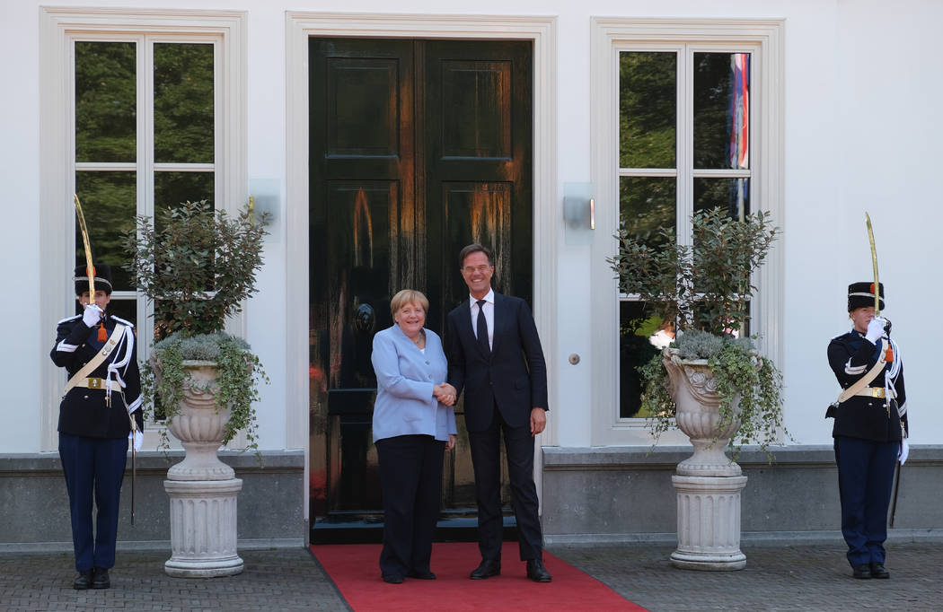 Dutch Prime Minister Mark Rutte, right, poses with German Chancellor Angela Merkel, at the entr ...