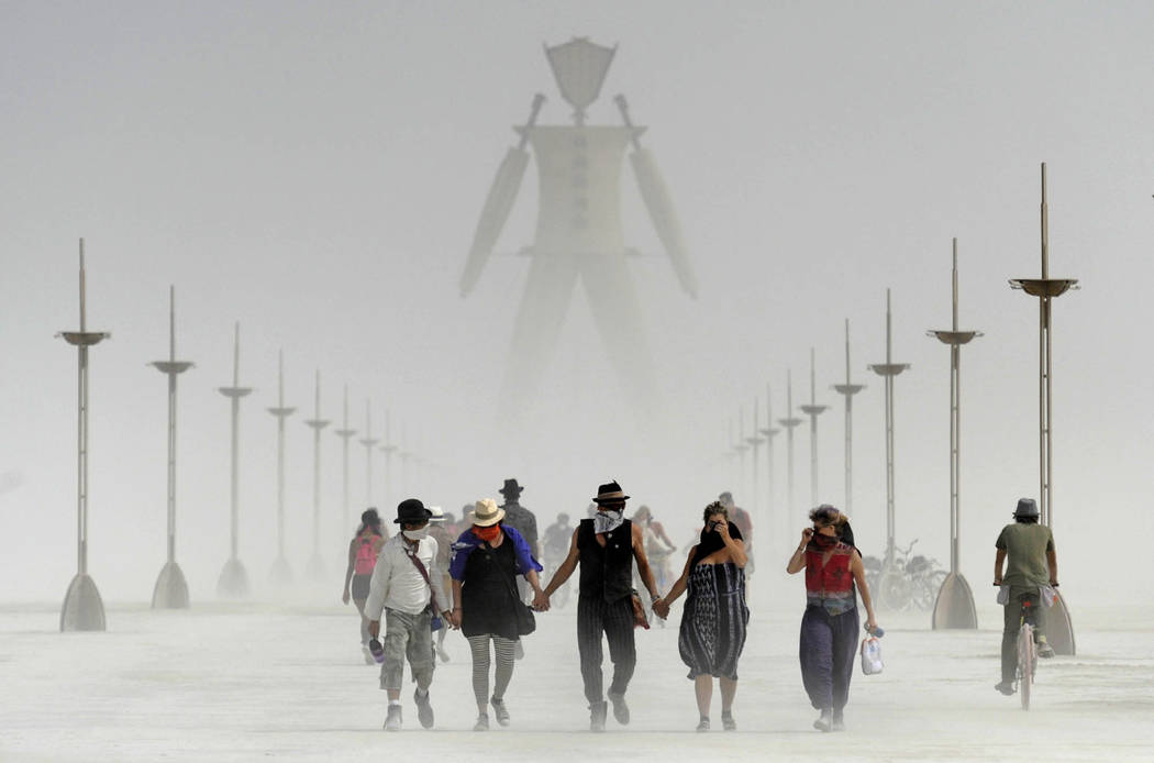 In this Aug. 29, 2014 file photo, Burning Man participants walk through dust at the annual Burn ...