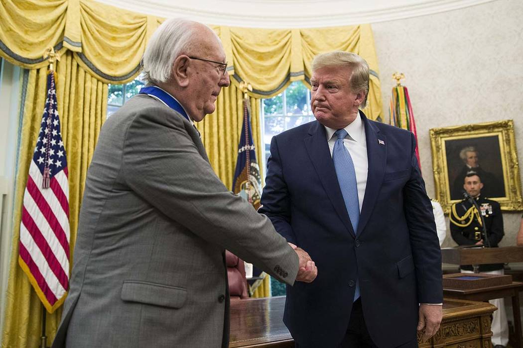 President Donald Trump shakes hands during a Presidential Medal of Freedom ceremony for former ...
