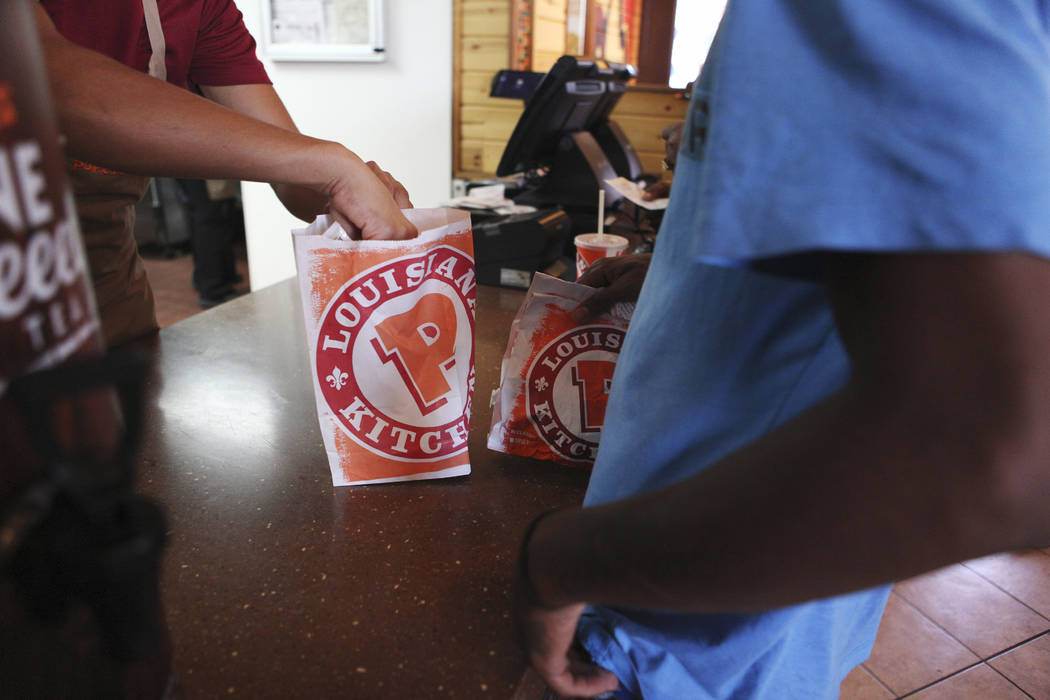 A customer receives his order of the new chicken sandwiches at Popeyes on the corner of Bonanza ...