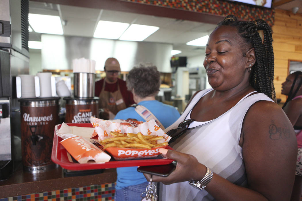 Janine Blake smiles after receiving her spicy chicken sandwich at Popeyes on the corner of Bona ...