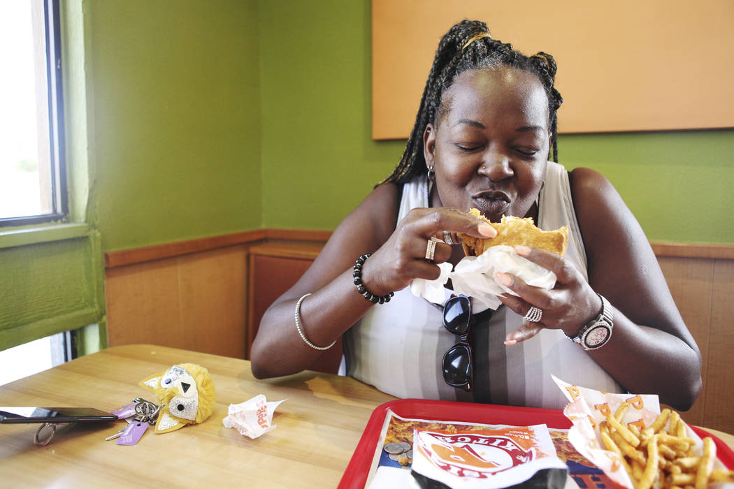 Janine Blake, of Las Vegas, rejoices after having a bite of the new spicy chicken sandwich at P ...