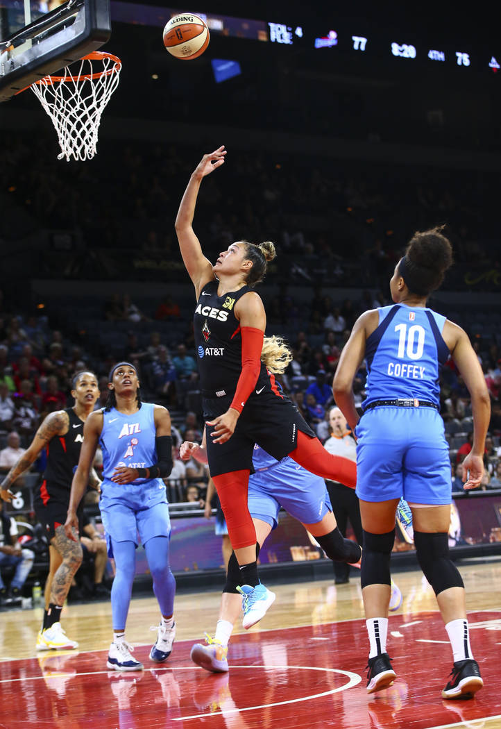 Las Vegas Aces' Kayla McBride goes to the basket in front of Atlanta Dream's Nia Coffey (10) du ...