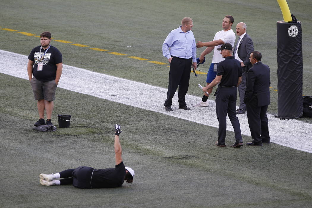 Officials assess the location where the CFL goal post holes were, before an NFL preseason footb ...
