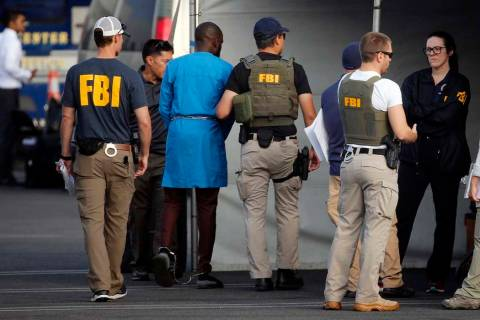 Federal agents hold a detainee, second from left, at a downtown Los Angeles parking lot after p ...