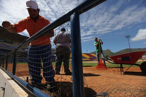 Ground workers fix the dugout of the Guatamare stadium in Porlamar at Margarita Island, Venezue ...