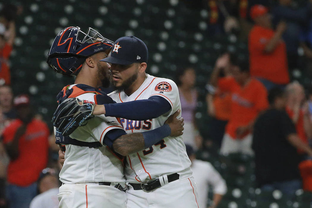 Houston Astros closer Roberto Osuna, right, celebrates with catcher Martin Maldonado as they de ...