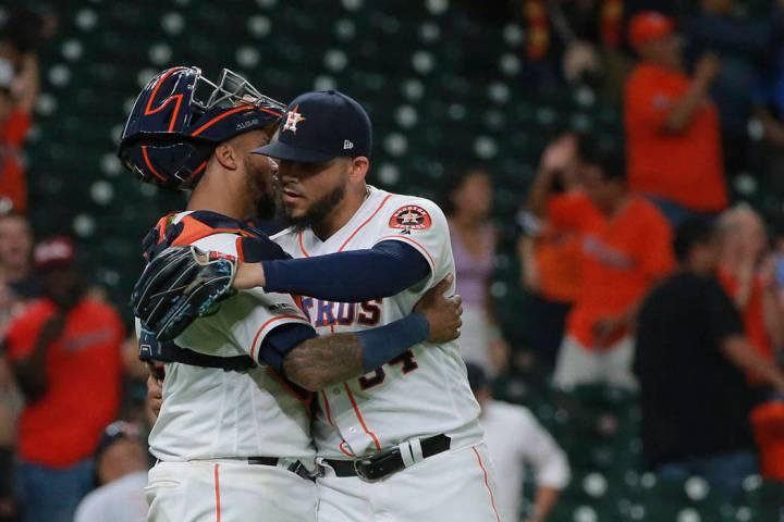 Houston Astros closer Roberto Osuna, right, celebrates with catcher Martin Maldonado as they de ...