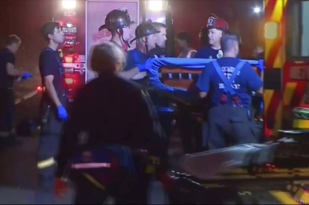In this image from video, an emergency crew carries stretchers for injured persons after a ligh ...