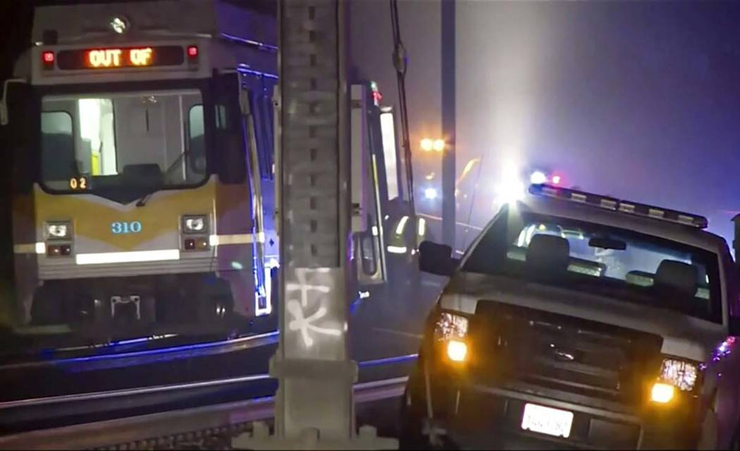 In this image from video, a light rail train, left, sits after derailment in Sacramento, Calif. ...