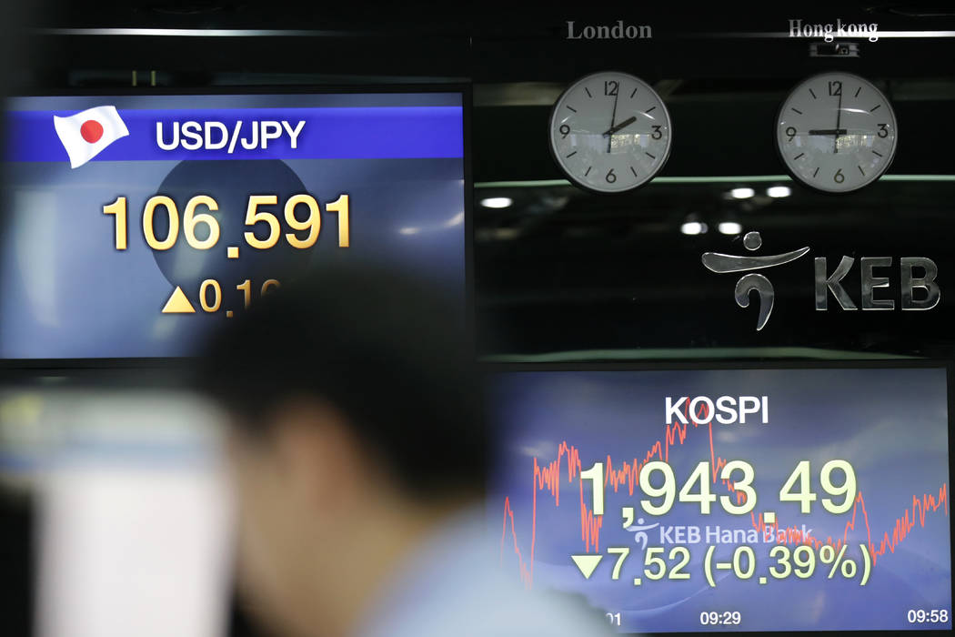 Screens showing the Korea Composite Stock Price Index (KOSPI) and the foreign exchange rates ar ...