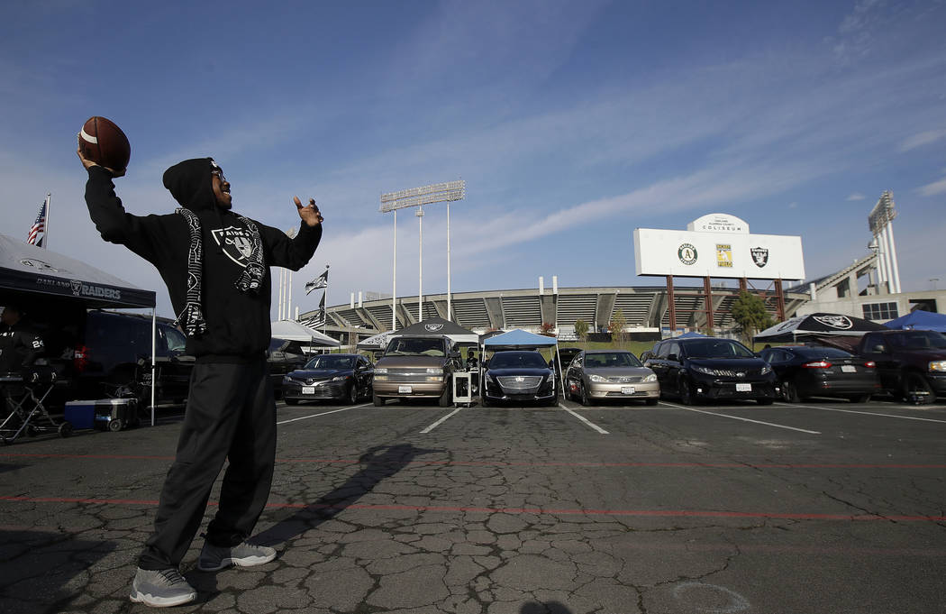 A Raiders fan throws a football as people tailgate outside Oakland Coliseum before an NFL footb ...
