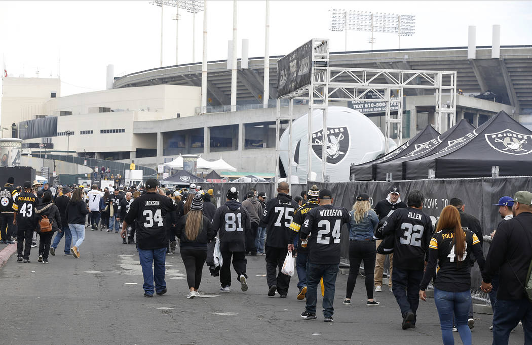 Fans tailgate outside of Oakland Alameda County Coliseum before an NFL football game between th ...