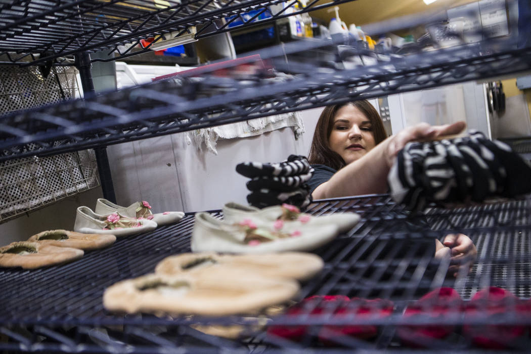 "Tyler Cecchini, crafts technician at Cirque du Soleil's ""O,"" organizes shoes in a wardrobe area ..."
