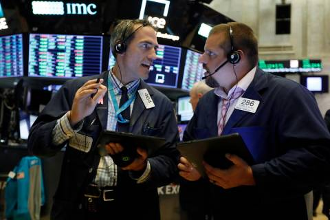 Traders Gregory Rowe, left, and Michael Milano work on the floor of the New York Stock Exchange ...