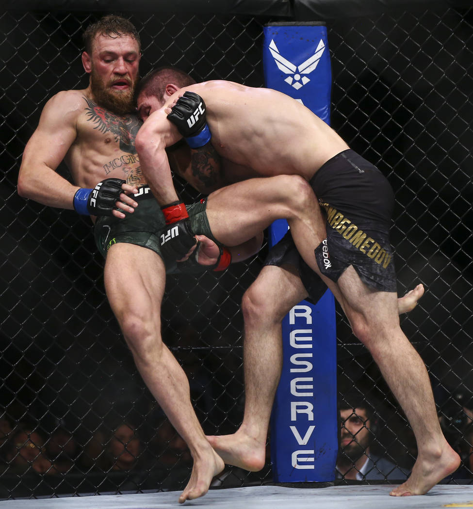 Khabib Nurmagomedov brings Conor McGregor to the mat during their lightweight title bout at UFC ...