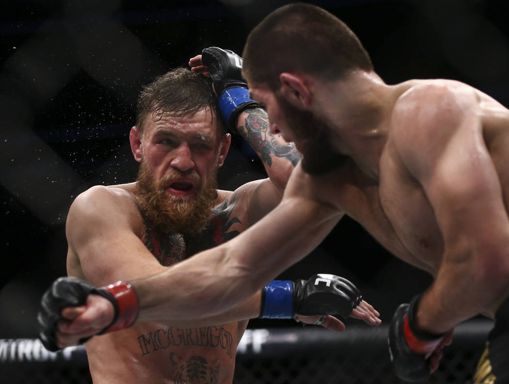 Conor McGregor, left, takes a hit from Khabib Nurmagomedov during their lightweight title bout ...
