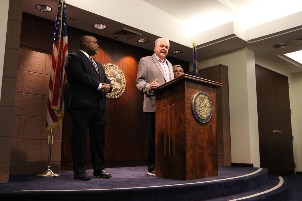 Gov. Steve Sisolak, center, speaks at a press conference at the Grant Sawyer State Office Build ...