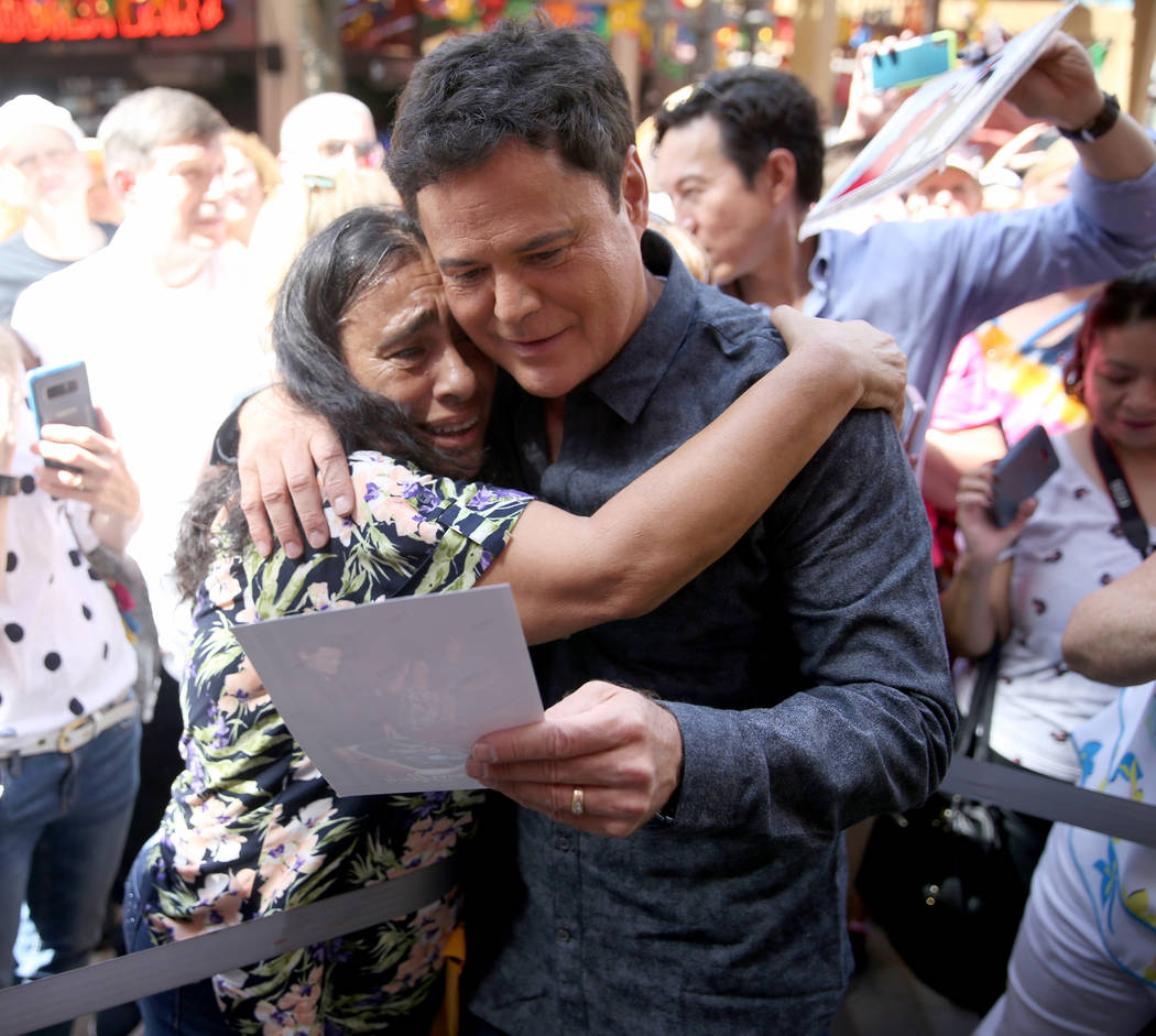Strip headliner Donny Osmond hugs Lucie Hanna of Canoga Park, Calif. after receiving a Key to T ...