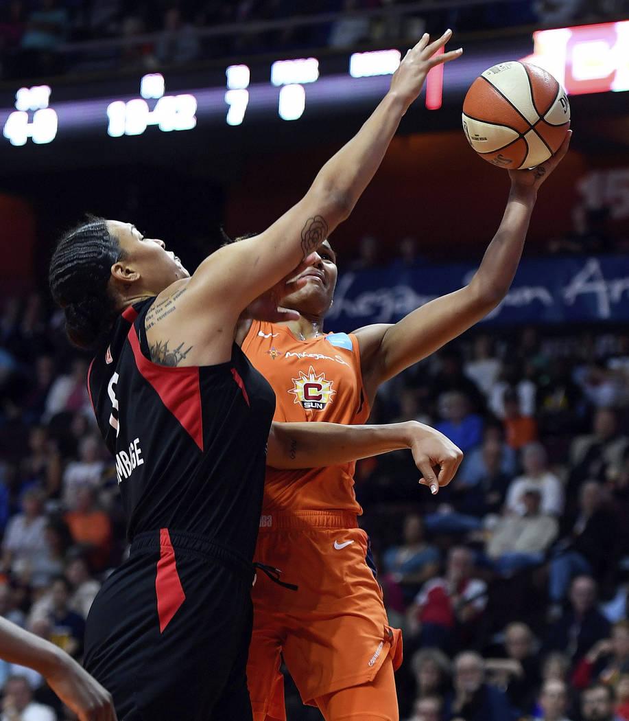 Connecticut Sun forward Alyssa Thomas scores around the defense of Las Vegas Aces center Liz Ca ...