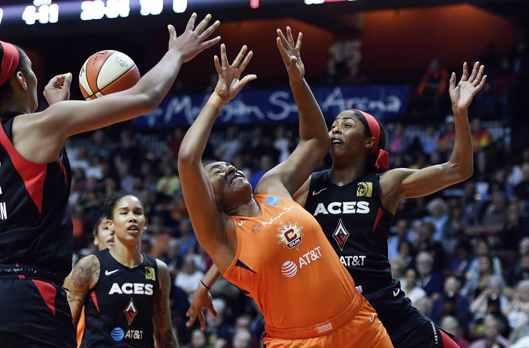 Connecticut Sun forward Morgan Tuck, center, is fouled by Las Vegas Aces guard Sydney Colson, r ...